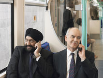 Businessmen Using Cellphones In Train Stock Images