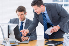 Businessmen using computer at office desk Stock Photo