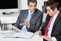 Businessmen Using Digital Tablet At Desk Stock Photo