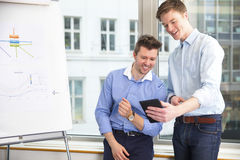 Businessmen Using Digital Tablet At Window Sill Royalty Free Stock Image