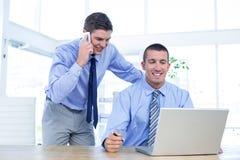 Businessmen using laptop Stock Images