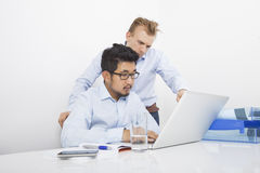 Businessmen using laptop together at desk in office Royalty Free Stock Photos