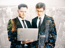 Businessmen using laptop. Two handsome young men using laptop on city background. Double exposure. Meeting concept Royalty Free Stock Images