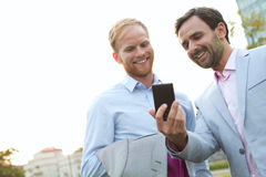 Businessmen using mobile phone against clear sky Royalty Free Stock Image