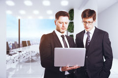 Businessmen using notebook. Attractive european businessmen using notebook in modern office with city view. Technology, communication and teamwork concept. 3D Stock Images