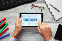 Businessmen using touchpad. Pressing Mortgage button. Stock Image