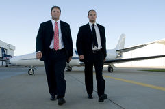 Businessmen walking away from corporate jet. Young businessmen walking away from corporate jet with serious looks royalty free stock photography