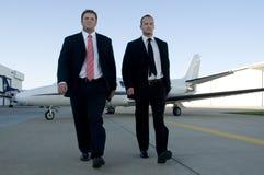 Businessmen walking away from corporate jet