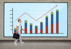 Businessmen walking. At big plasma panel with chart on wall Royalty Free Stock Image