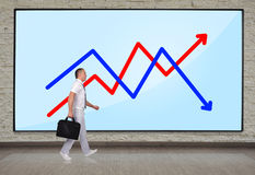 Businessmen walking. At big plasma panel with pie chart on wall Stock Photo