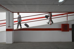 Businessmen Walking Down Ramp With Luggage In Parking Garage Stock Photo