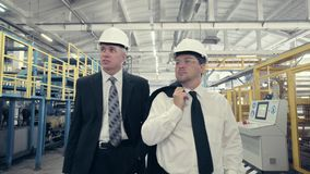 Businessmen walking through factory and talking stock video