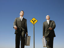 Businessmen Walking Past Road Sign Royalty Free Stock Image