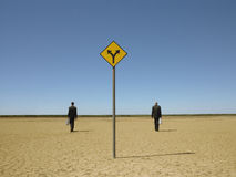 Businessmen Walking Past Road Sign In Desert Royalty Free Stock Images