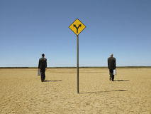 Businessmen Walking Past Road Sign In Desert Stock Images