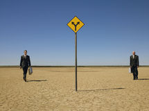 Businessmen Walking Towards Road Sign In Desert Royalty Free Stock Photo