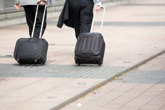Businessmen walking with wheeled luggage Stock Images