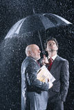 Businessmen Watching Rain From Under Umbrella Stock Photography