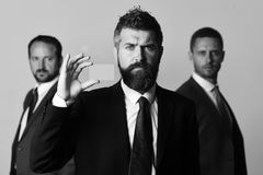 Businessmen wear smart suits and ties. Men with beard and serious faces advertise company and partnership. Leaders hold business card on light grey background Royalty Free Stock Image