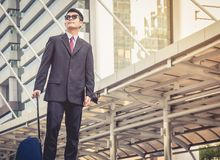 Businessmen wearing sunglasses are traveling with their luggage stock photography