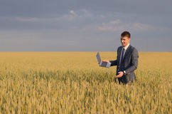 Businessmen in a wheat field. Successful man on the field with laptop Royalty Free Stock Photo