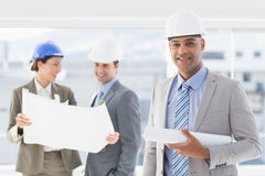 Businessmen and a woman with hard hats and holding blueprint Royalty Free Stock Images