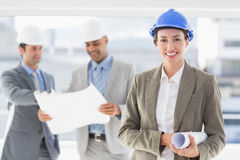 Businessmen and a woman with hard hats and holding blueprint Stock Images