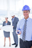 Businessmen and a woman with hard hats and holding blueprint Royalty Free Stock Photo