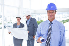 Businessmen and a woman with hard hats and holding blueprint Royalty Free Stock Photography