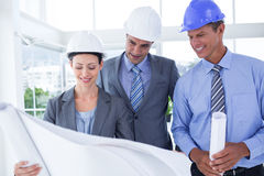 Businessmen and a woman with hard hats and holding blueprint Stock Photos