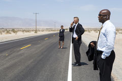 Businessmen and woman on open road in desert using mobile phones, side view Stock Photos