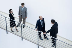 Businessmen and woman standing together by railing and conversing Royalty Free Stock Photos
