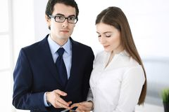 Businessmen and woman using tablet computer in modern office. Colleagues or company managers at workplace. Partners stock photo