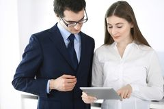 Businessmen and woman using tablet computer in modern office. Colleagues or company managers at workplace. Partners royalty free stock photos