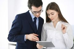 Businessmen and woman using tablet computer in modern office. Colleagues or company managers at workplace. Partners royalty free stock image