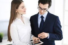 Businessmen and woman using tablet computer in modern office. Colleagues or company managers at workplace. Partners stock image