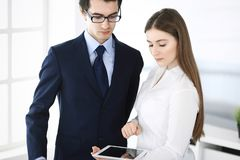 Businessmen and woman using tablet computer in modern office. Colleagues or company managers at workplace. Partners stock photos