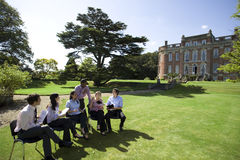 Businessmen and women with folders in grounds by manor house Stock Images