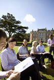 Businessmen and women with folders in grounds by manor house Stock Photography