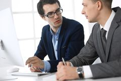 Businessmen working with computer in modern office. Headshot of male entrepreneur or company manager at workplace. Partners discussing contract. Business stock photos