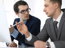 Businessmen working with computer in modern office. Headshot of male entrepreneur or company manager at workplace. Partners discussing contract. Business stock photography