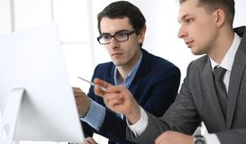 Businessmen working with computer in modern office. Headshot of male entrepreneur or company manager at workplace. Partners discussing contract. Business stock image
