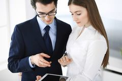 Businessmen and woman using tablet computer in modern office. Colleagues or company managers at workplace. Partners royalty free stock photo