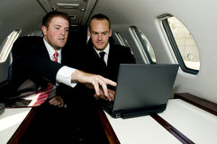 Businessmen working on a corporate jet. Young businessmen working on a laptop in a corporate jet Stock Photography