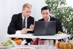 Businessmen working and eating lunch Stock Photography