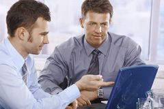 Businessmen working on laptop. Looking at screen, pointing in the office Stock Image