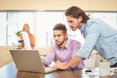 Businessmen working on laptop with female colleague in background Royalty Free Stock Photos
