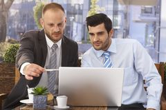 Businessmen working on laptop at outdoor cafe Royalty Free Stock Photo