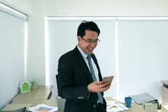 Businessmen are working on a mobile phone. Businessmen are working on a mobile phone at office Royalty Free Stock Image