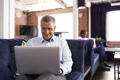 Businessmen Working On Sofas In Relaxation Area Of Office Royalty Free Stock Image